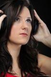 Молодая женщина слушая к музыке на шлемофоне Стоковые Изображения