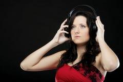Молодая женщина слушая к музыке на шлемофоне Стоковое Фото