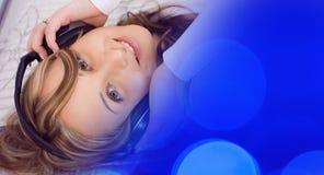 Молодая женщина слушая к музыке, синь освещает предпосылку Стоковые Изображения