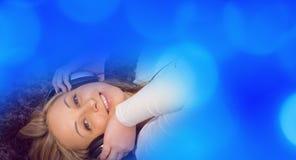 Молодая женщина слушая к светам музыки голубым defocused Стоковое Изображение RF