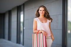 Молодая женщина с хозяйственной сумкой на переулке мола Стоковое фото RF