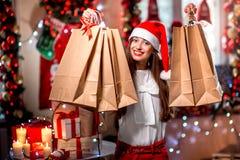 Молодая женщина с хозяйственными сумками на рождестве Стоковые Изображения