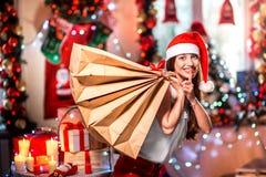 Молодая женщина с хозяйственными сумками на рождестве Стоковая Фотография