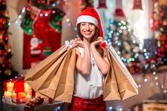 Молодая женщина с хозяйственными сумками на рождестве Стоковое Изображение