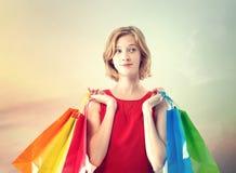 Молодая женщина с цветастыми хозяйственными сумками Стоковые Фотографии RF
