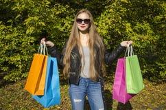 Молодая женщина с цветастыми хозяйственными сумками Стоковая Фотография