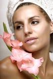 Молодая женщина с цветком и полотенцем Стоковое Фото