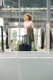 Молодая женщина с чемоданом на эскалаторе Стоковая Фотография