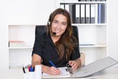 Молодая женщина с шлемофоном пишет в файл Стоковые Фото