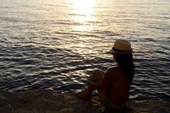 Молодая женщина с шляпой на заходе солнца Стоковое фото RF