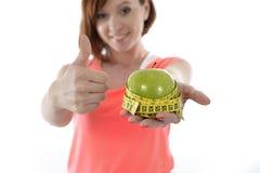 Молодая женщина с яблоком и лентой измерения стоковая фотография rf
