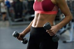 Молодая женщина с dumbells красивого брюшка поднимаясь на спортзале стоковое фото