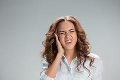Молодая женщина с earache над серым цветом Стоковые Изображения RF