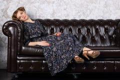 Молодая женщина с hairdo в платье лежит на черной кожаной софе стоковые фото