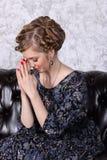 Молодая женщина с hairdo молит с закрывая глазами на софе стоковые изображения rf