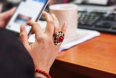 Молодая женщина с smartphone в руке, defocuses клавиатуры Стоковая Фотография RF