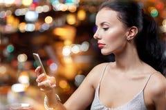 Молодая женщина с smartphone на ночном клубе или баре Стоковое Изображение RF