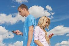 Молодая женщина с sms чтения человека стоковое изображение rf