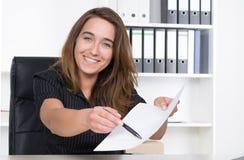 Молодая женщина указывает на документ с ручкой Стоковая Фотография RF