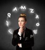 Молодая женщина думая с циркуляцией письма вокруг ее головы Стоковое Изображение RF