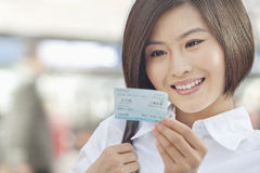 Молодая женщина усмехаясь и смотря билет на поезд стоковое изображение