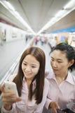Молодая женщина 2 усмехаясь и смотря на телефоне внутри помещения в моле Стоковая Фотография RF