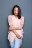 Молодая женщина усмехаясь на серой предпосылке стоковая фотография rf