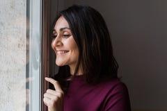 Молодая женщина усмехаясь окном Стоковая Фотография RF