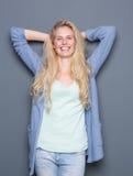Молодая женщина усмехаясь с руками за головой стоковое фото