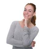 Молодая женщина усмехаясь с рукой на подбородке Стоковые Фотографии RF
