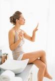 Молодая женщина дуя на ногтях после прикладывать маникюр Стоковые Изображения RF