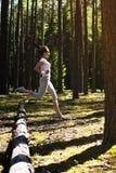 Молодая женщина фитнеса бежать и скача над журналами пока на весьма внешней тренировке фитнеса в лесе Стоковая Фотография