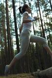 Молодая женщина фитнеса бежать и скача над журналами пока на весьма внешней тренировке фитнеса в лесе Стоковое Изображение