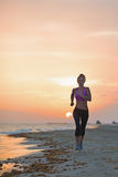 Молодая женщина фитнеса бежать на пляже в вечере стоковое изображение rf