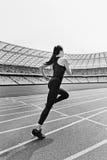 Молодая женщина фитнеса в sportswear бежать на идущем стадионе следа Стоковые Фотографии RF