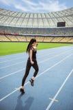 Молодая женщина фитнеса в sportswear sprinting на идущем стадионе следа Стоковое Изображение
