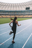 Молодая женщина фитнеса в sportswear sprinting на идущем стадионе следа Стоковая Фотография RF