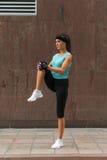 Молодая женщина фитнеса делая тренировку подогрева перед бежать протягивающ ее ногу путем выполняя колено к простиранию комода на Стоковые Изображения