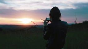 Молодая женщина фотографирует заход солнца с smartphone Рискованное предприятие и конец-вверх сток-видео