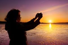 Молодая женщина фотографируя, selfie, на пляже во время захода солнца Стоковое фото RF