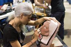 Молодая женщина художника тщательно ваяет детали маски ужаса Стоковое фото RF