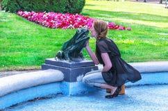 Молодая женщина целует скульптуру лягушки Стоковая Фотография RF
