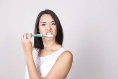 Молодая женщина чистя ее зубы щеткой изолированные над белой предпосылкой стоковое изображение