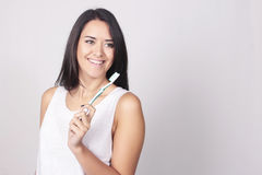Молодая женщина чистя ее зубы щеткой изолированные над белой предпосылкой стоковые фотографии rf