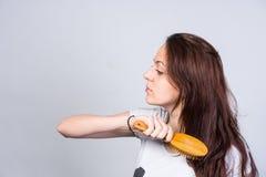 Молодая женщина чистя ее длинные коричневые волосы щеткой Стоковое Изображение