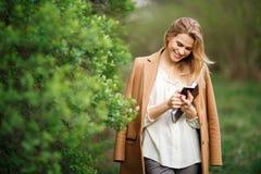 Молодая женщина читает сообщения на ее мобильном телефоне Стоковое фото RF