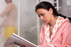 Молодая женщина читая газету и ждать ее wh парня Стоковое фото RF