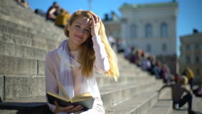 Молодая женщина читая книгу и усмехаясь на камере на лестницах снаружи акции видеоматериалы