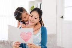 Молодая женщина читая подарок карточки дня ` s матери стоковые фотографии rf