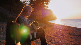 Молодая женщина читая eBook в парке на береге озера или моря Сидящ на стенде на заходе солнца, в оружиях сток-видео